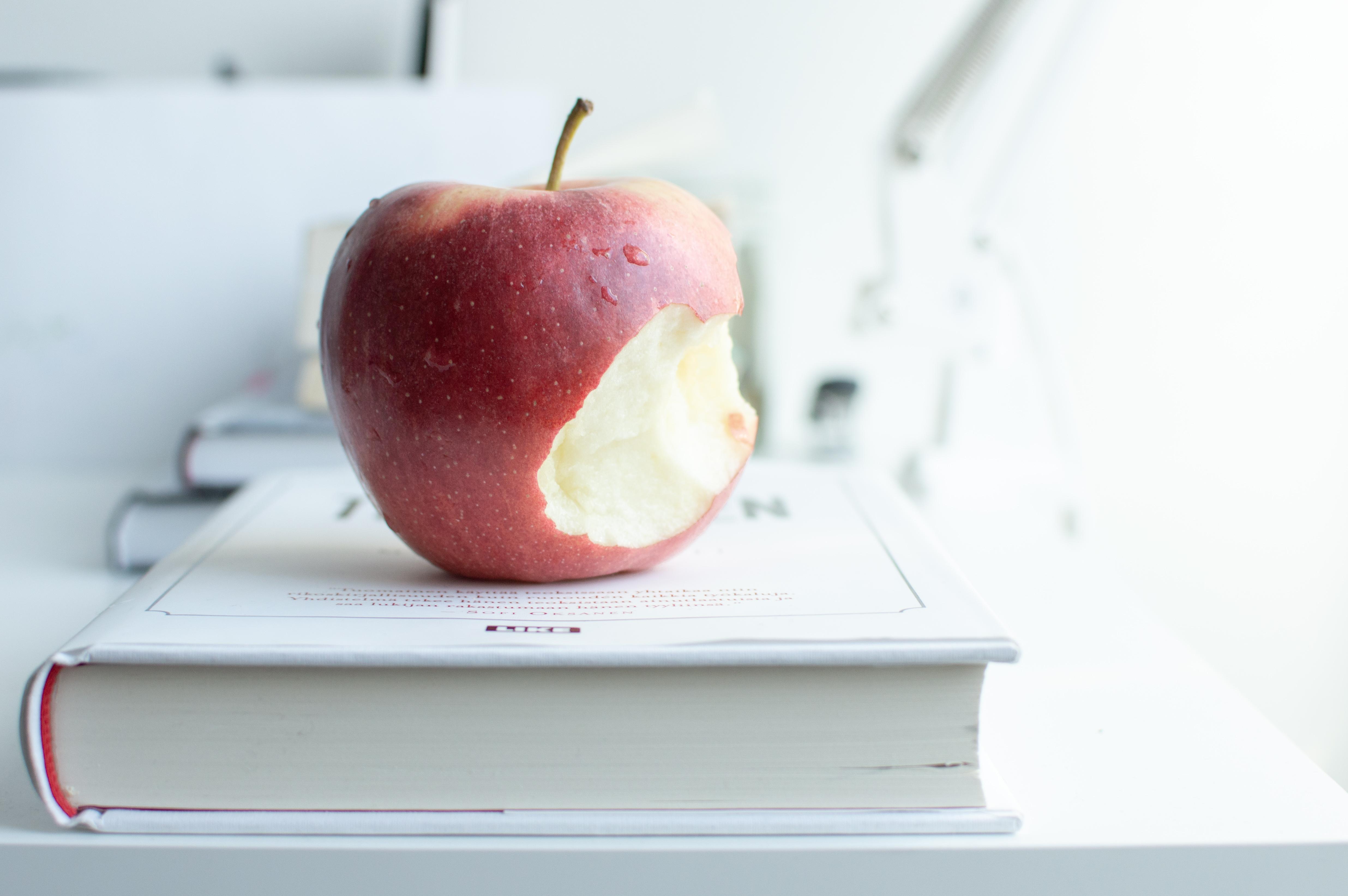 Osittain syöty omena ja kirja. Lukeminen tuo viisautta.